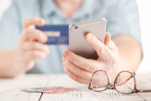 Close up male hands holding credit card and using mobile smart phone
