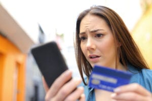 Worried woman pays online with credit card and smart phone