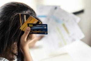 woman stressed holding credit cards