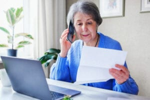 An elderly woman alls on the phone and finds out information about a loan or her savings